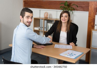 Young Business woman looking at camera while shaking hand at office desk