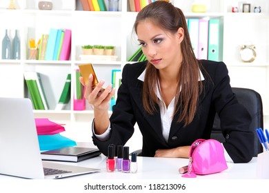 young business woman looking in the mirror at her workplace