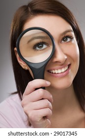 Young business woman looking through loupe close up