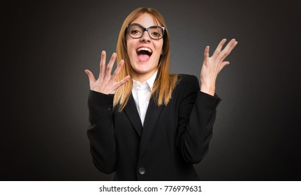 Young business woman making surprise gesture on dark background