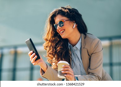 Young business woman making video call via smartphone and wireless earphones in the city