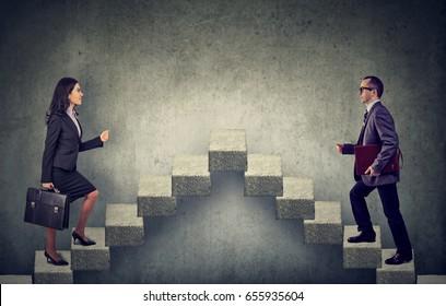 Young business woman and man stepping up a stairway career ladder