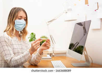 Young business woman measuring fever and wearing protective mask, working from home