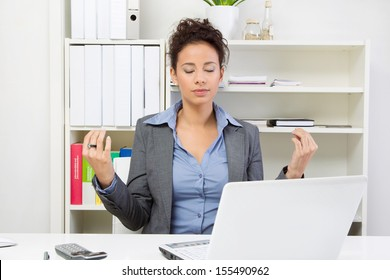 Young business woman meditating in office