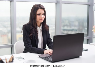 Young business woman with notebook in the office, workplace.