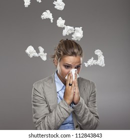 Young business woman in office under the rain of paper handkerchiefs - girl got a cold with lot of tissues