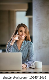 Young business woman on the phone at office. Business woman speaking on the phone and working on laptop. Pretty young business woman sitting on workplace.  Smiling woman working in the office.