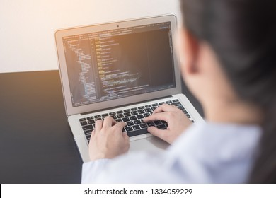 Young business woman programmer working at office. woman hands coding and programming on screen laptop, in programming concept