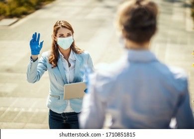 Young business woman with protective mask on her face is going to work at they say hello to her friend during covid19 pandemic.