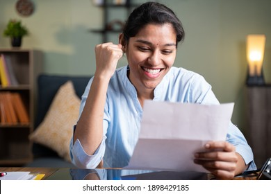 Young business woman reading paper letter feeling overjoyed and enjoying by good news clenched fist - Concept of new Job offer or promotion, college admission and loan approvel