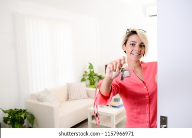 young business woman real estate agent giving keys of new house student apartment