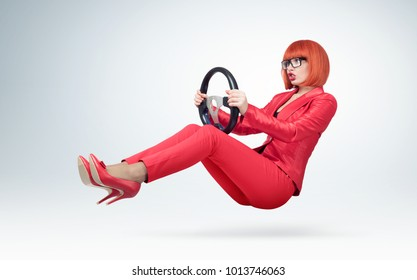Young business woman in red and glasses driver car with a wheel, auto lady concept.