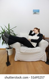 A young business woman relaxing in an armchair after work