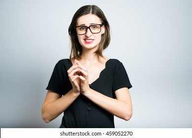 Young business woman says oops, studio photo isolated on a gray background