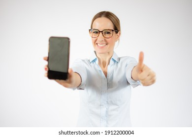 Young business woman showing smart phone with thumb up over white background.