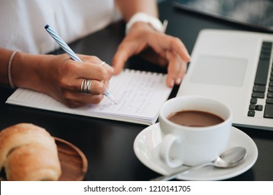 Young business woman sitting in cafe and taking notes in notebook. On table is laptop, croissant and a cup of coffee. Student learning online. Blogger.