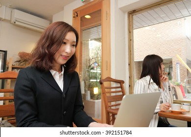 A young business woman sitting in a cafe with a laptop