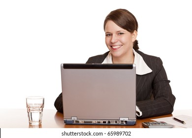 Young business woman sitting happy in office and works on computer. Isolated on white background.