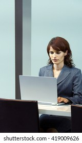 Young business woman sitting at her desk in an office, working on a laptop computer