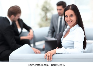 young business woman sitting in office at background business team