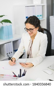 young business woman sitting at the office desk and writing some notes