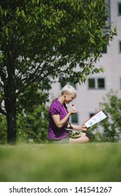 young business woman sitting on grass in park, eating salad for lunch and reading paperwork