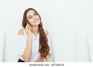 Young business woman sitting on chair and using mobile phone. talking on the mobile