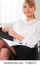 young business woman is sitting on sofa at modern office
