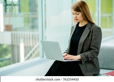 Young business woman sitting at sofa and working with laptop at the waiting hall of the business center.