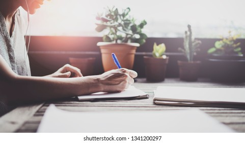 Young business woman sitting at table in caffee terrace and taking notes in notebook.On table is smartphone and paper documents. Student learning online or blogger concept
