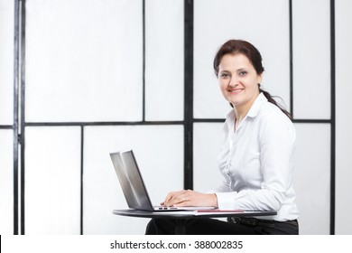 Young business woman sitting at table with a laptop
