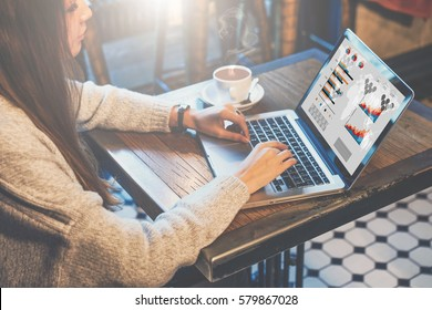 Young business woman sitting at table in coffee shop and typing on laptop. Graphics and diagrams on computer screen. Woman analyzing data. Student learning online. Freelancer working home, blogging.