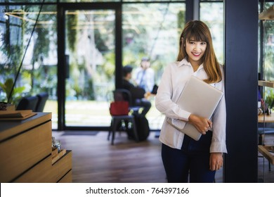 Young business woman standing in the cafe and holding a laptop in her hand