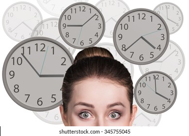 Young business woman stands among big clocks