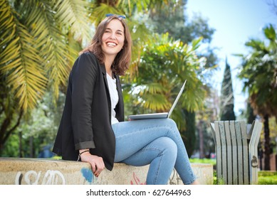 A young business woman, a student or freelancer working outside and enjoying her freedom. Studying on a campus or summer school abroad. A background of blurred palm tree leaves and blue sky.