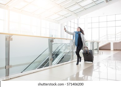 Young business woman with suitcase running to catch the plane or train in before it leaves the station without her.