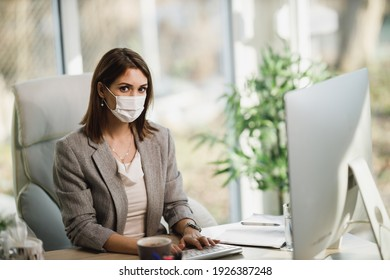 A young business woman with surgical mask sitting alone in her office and looking at camera.
