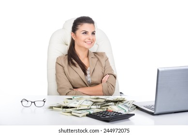 A young business woman at the table with a lot of money and laptop.