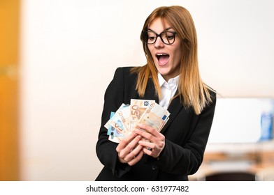 Young business woman taking a lot of money on unfocused background