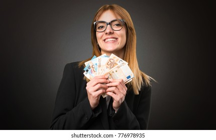 Young business woman taking a lot of money on dark background