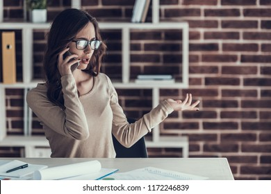 Young Business Woman Talking on Cellphone at Home. Beautiful Woman wearing Glasses Sitting at Desk Talking on Phone and Arguing. Businesswoman Working Remotely at Home. Homeoffice Concept
