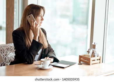 Young business woman talking on the phone in coffee shop.
