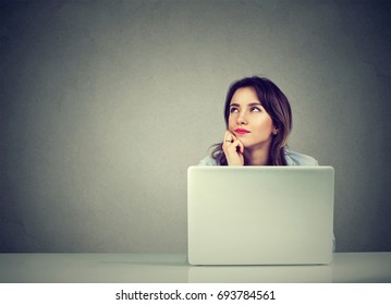 young business woman thinking daydreaming sitting at desk with laptop computer