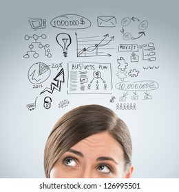 Young business woman thinking of her plans closeup face portrait and sketches overhead