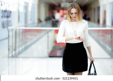 Young business woman in trendy casual wear hurrying, waiting impatient, looking at her watch in a rush, running errands, copy space