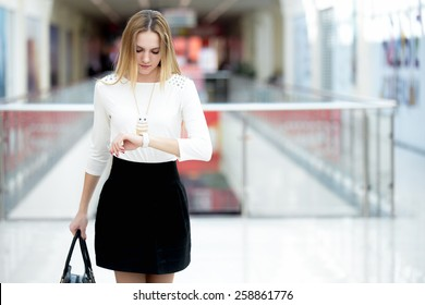 Young business woman in trendy wear hurrying, waiting impatient, looking at her watch in a rush, running errands, copy space