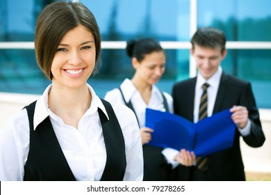 Young business woman with two of her co-workers on background  modern office building