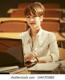 Young business woman using laptop at sidewalk cafe Stylish fashion female model in white shirt with pixie hairstyle