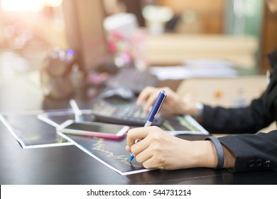Young business woman using a phone and calculator in her office , and economic analysis ,soft focus for create text