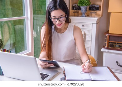 A young business woman using tablet and write it on paper at her modern office, Looking for direction and inspiration.